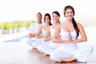 Group of people doing yoga exercises and smiling